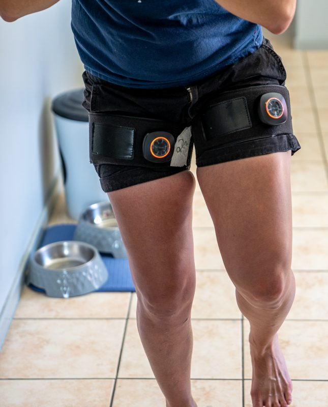 Client performing single leg squats with blood pressure cuffs on her thighs to complete BFR training post ACL rupture