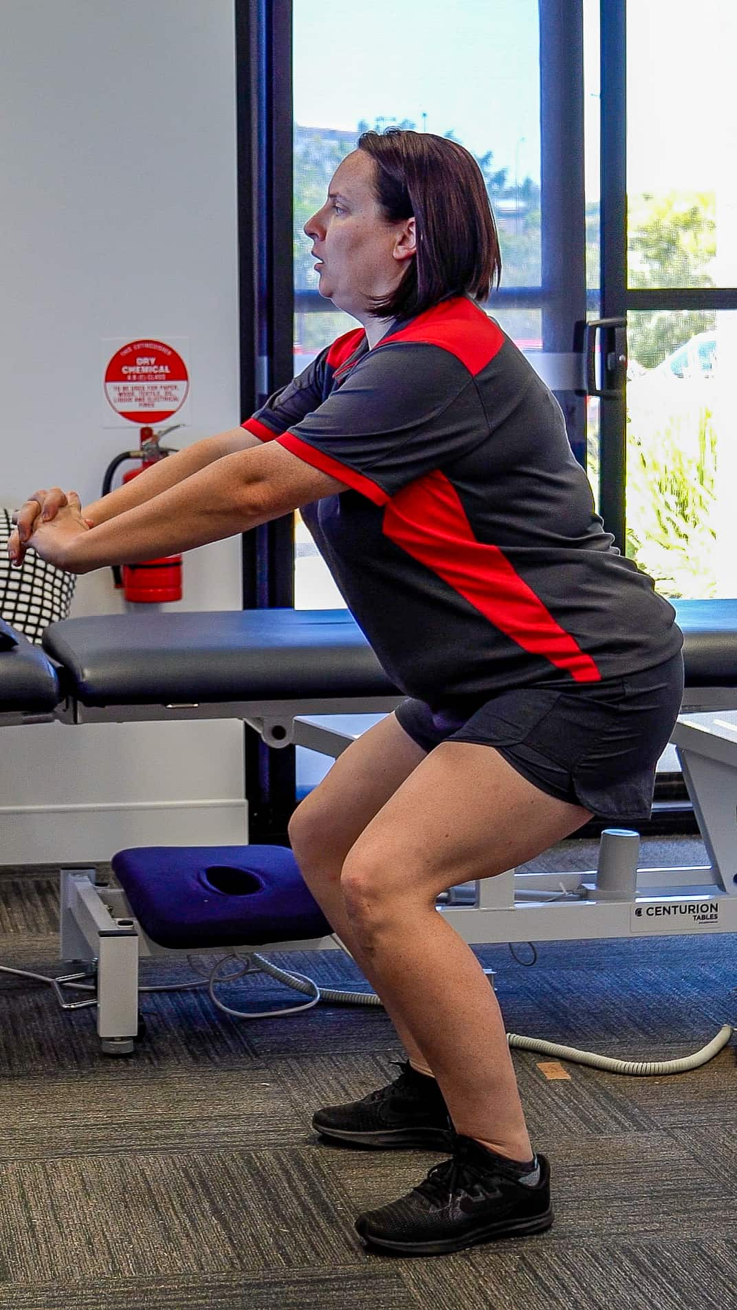 Client performing a squatting exercise to assist in her recovery.