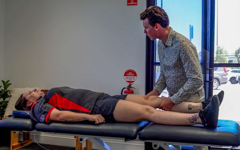 Performing a Lachmann's test on a clients knee to assess for a potential ACL rupture